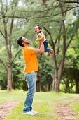 happy young father playing with son outdoors