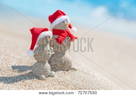 Snowmans Couple At Sea Beach In Christmas Hat. New Years Holiday