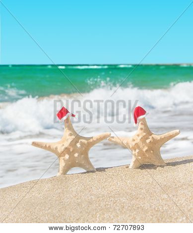 Sea-stars Couple In Santa Hats Walking At Sea Beach. New Years D