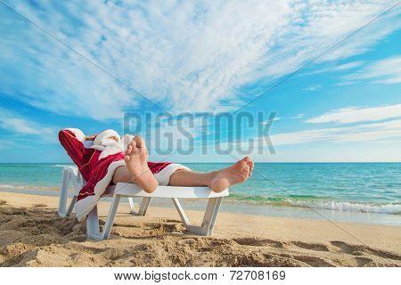Sunbathing Santa Claus Relaxing In Bedstone On Tropical Sandy Be