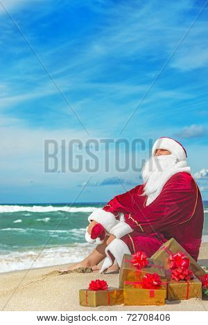 Santa Claus With Many Golden Gifts Relaxing At Beach