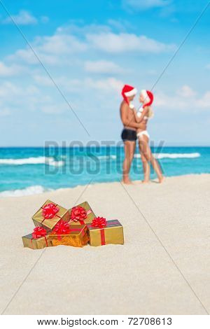 Kissing Couple In Santa Hats At Sea Beach With Christmas Golden gifts