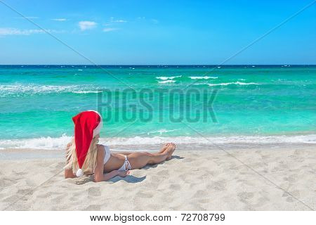 Beautiful Blonde Woman In Bikini And Red Christmas Hat On Sea Beach.