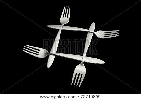 Four Interlaced Silver Forks On Black