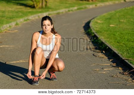 Female Runner Lacing Sport Shoes Before Running In Park