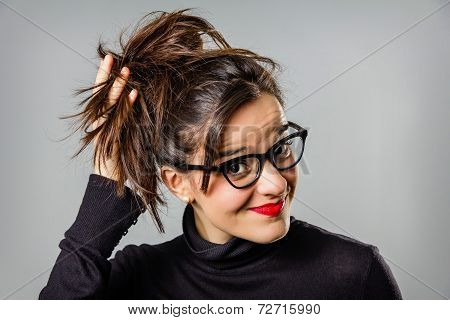 Real girl with glasses and red lips touching her hair bun