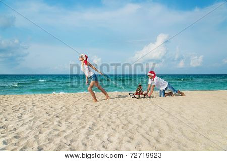 Young Couple Running At Sea Beach In Santa Hats With Sled And decorated christmas tree