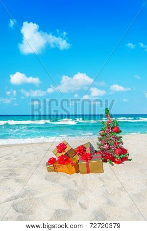 Christmas Tree And Golden Gift With Big Red Bow On The Sea Beach. Christmas Vacation Concept.