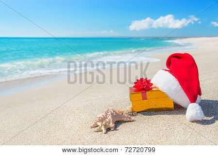 Santa Claus Hat And Christmas Gift Box On Seashore With Sea stars