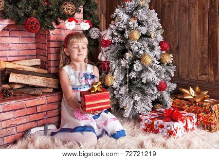 Happy small girl with christmas gift box in home comfortable interior