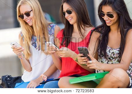 Three Girls Chatting With Their Smartphones At The Park