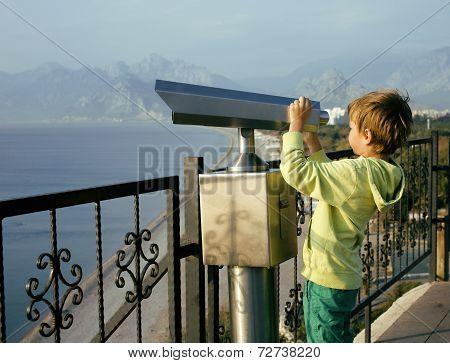 little cute boy looking through telescope at sea viewpoint in Ataturk park