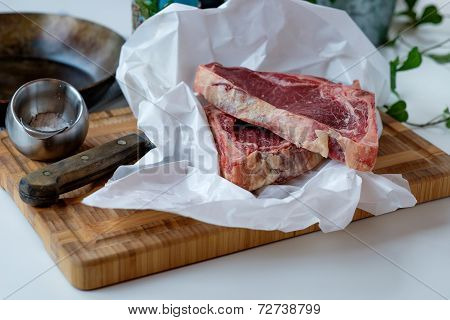 Cuts Of Raw Beef On The Cutting Board With Some Green Salad In The Background