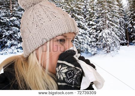 Young Woman With A Cold And Flu Virus Sneezing Into A Tissue Outdoors