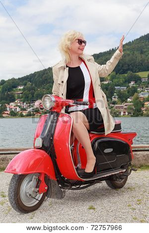 Blonde woman goes waving with the scooter on the lake