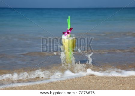 Glass Of Cocktail In The Sand Splashed By Waves