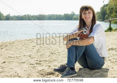 Smiling Hipster Woman Posing With Old Film Camera At The Beach