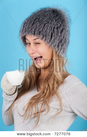 Winked Woman Holding A Cup With Hot Drinks