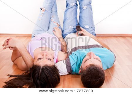 Happy Couple On Floor Listening Music