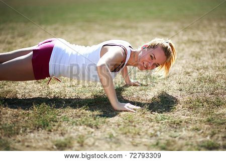 Young Woman Doing Push Ups Exercise, Workout On Grass Field