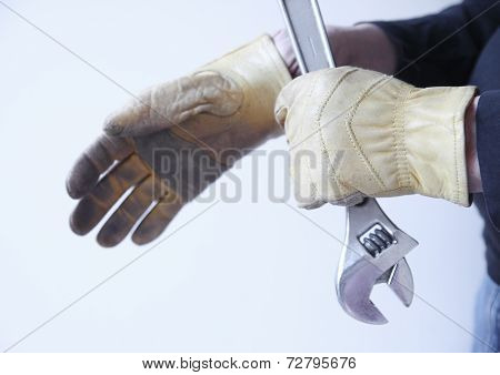 Workman with tool pulls on gloves