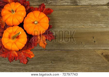 Autumn leaves and pumpkins on wood