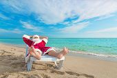 image of sunbather  - sunbathing Santa Claus relaxing in bedstone on tropical sandy beach  - JPG