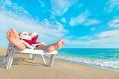 foto of sunbather  - sunbathing Santa Claus relaxing tropical sandy beach  - JPG