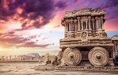 image of chariot  - Stone chariot in courtyard of Vittala Temple at sunset purple sky in Hampi Karnataka India - JPG