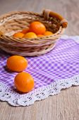picture of kumquat  - Ripe fruit kumquat orange lying on a wooden surface against the background of a wicker basket - JPG