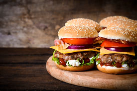 picture of takeaway  - Beef burgers on the wooden background with blank space on left side [[** Note: Shallow depth of field ** Note: Visible grain at 100%, best at smaller sizes - JPG