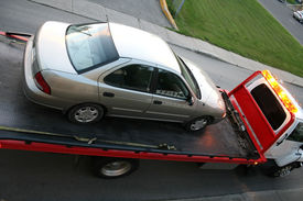 stock photo of towing  - Car being towed on a flatbed truck - JPG