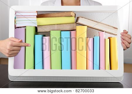 E-learning concept.  Digital library - books inside tablet