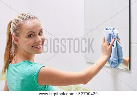 people, housework and housekeeping concept - happy woman cleaning mirror with rag at home