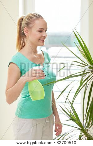 people, housework and care concept - happy woman with spray bottle spraying houseplants at home