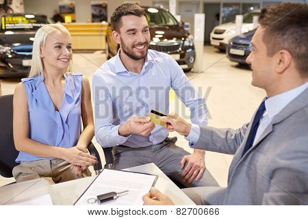 auto business, sale and people concept - happy couple with dealer buying car in auto show or salon
