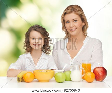 people, healthy lifestyle, family and food concept - happy mother and daughter eating healthy breakfast over green background