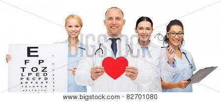 medicine, profession, teamwork and healthcare concept - international group of smiling medics or doctors with clipboard and stethoscopes holding red paper heart shape over white background
