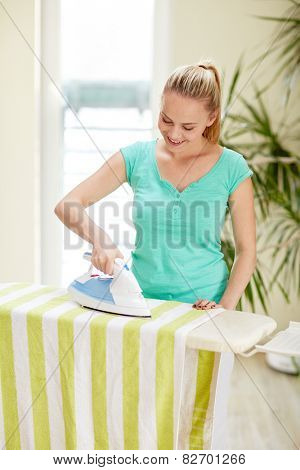 people, housework, laundry and housekeeping concept - happy woman with iron and ironing board at home