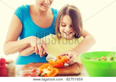 family, child, cooking and home concept - smiling little girl with mother chopping pepper in the kitchen