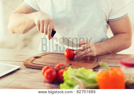 cooking and home concept - close up of male hand cutting tomato on cutting board with sharp knife