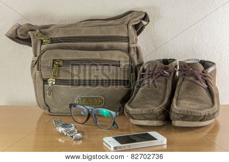 Still Life With Casual Man, Boots And Bag On Wooden Table Over Grunge Background