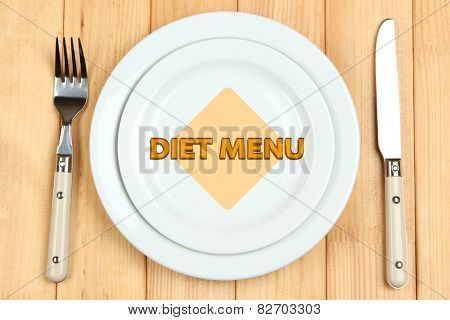 Plate with text Diet Menu, fork and knife on wooden background