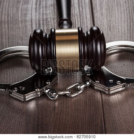 handcuffs and judge gavel on brown wooden table
