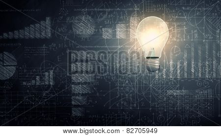 Glowing light bulb with sketches at background