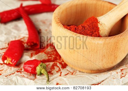 Ground red pepper in mortar with chili pepper on table close up