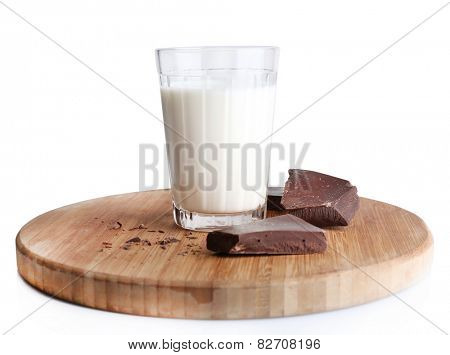 Glass of milk with chocolate chunks on wooden cutting board isolated on white