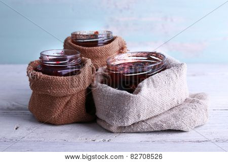 Homemade jars of fruits jam in burlap pouches on wooden table and color wall background