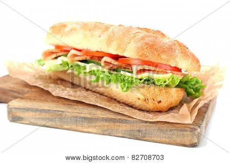 Fresh sandwich on wooden cutting board isolated on white