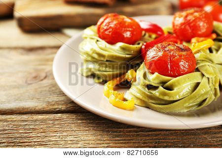 Tasty green pasta with pepper, and tomatoes on wooden table background